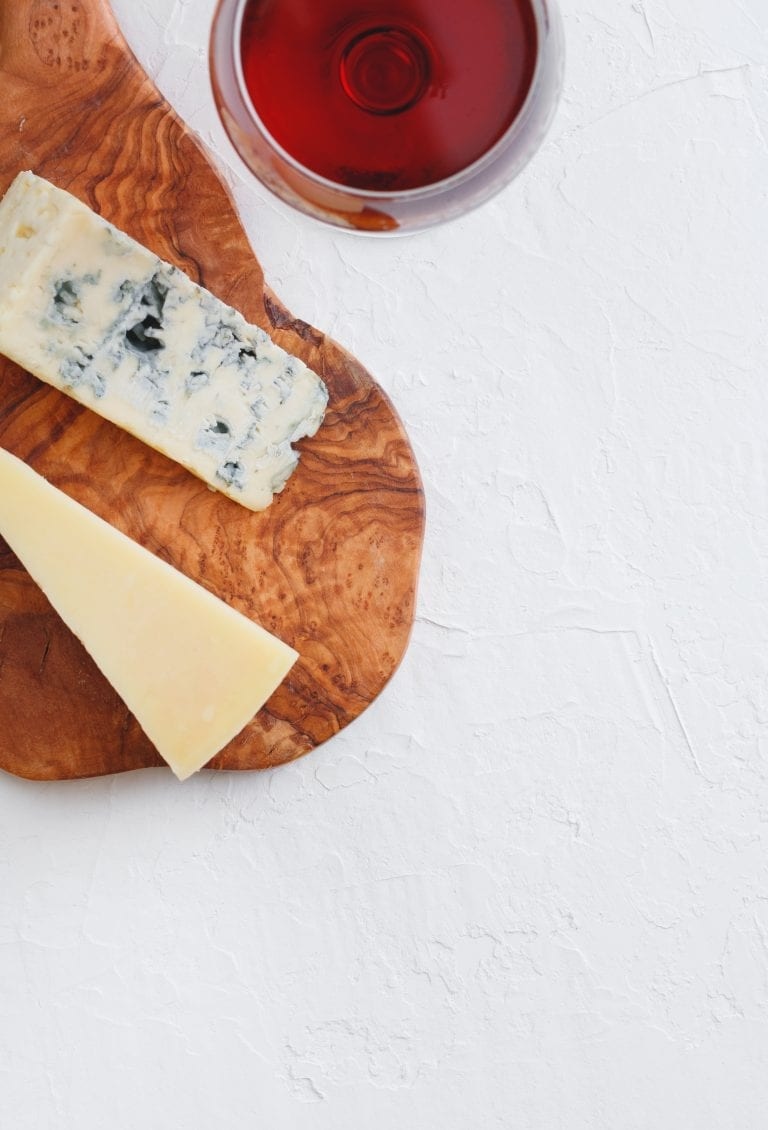 glass of red wine with blue cheese on a wooden cheeseboard