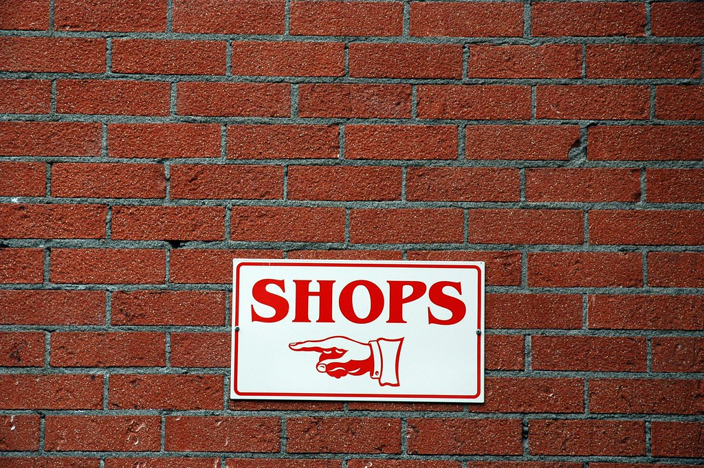 shop sign on a red brick wall