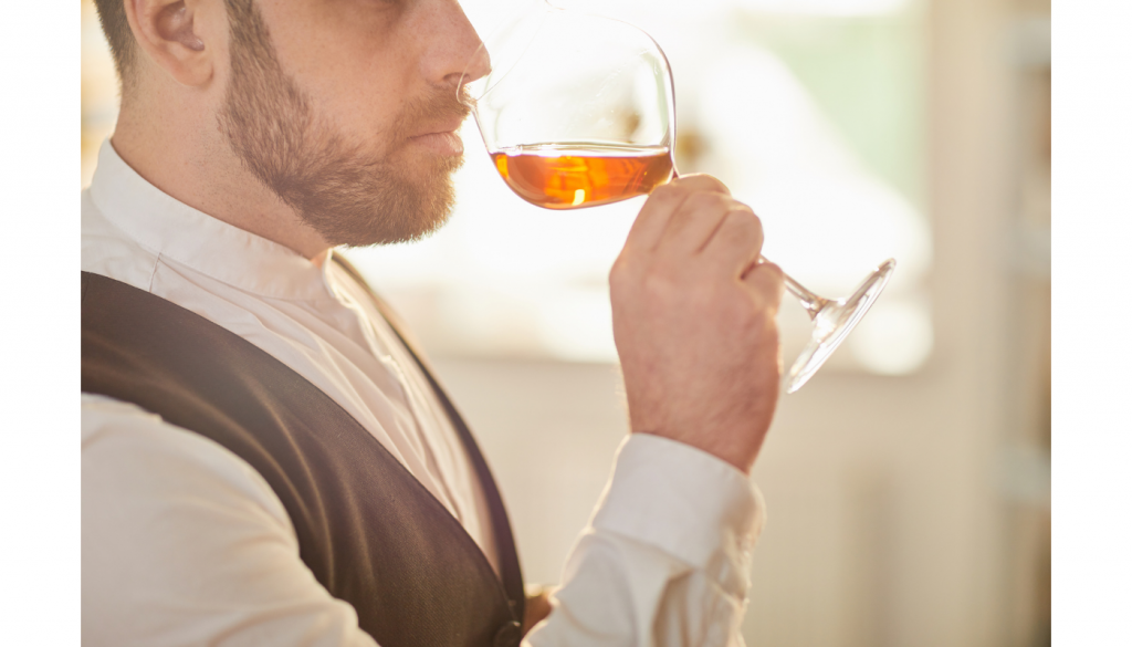 A sommelier sniffing rosé wine out of a wine glass
